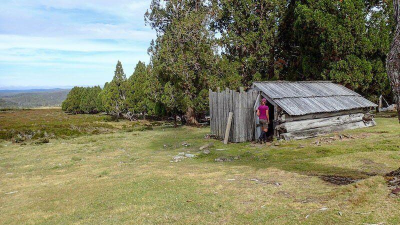 female hiker enters mountain hut tasmania