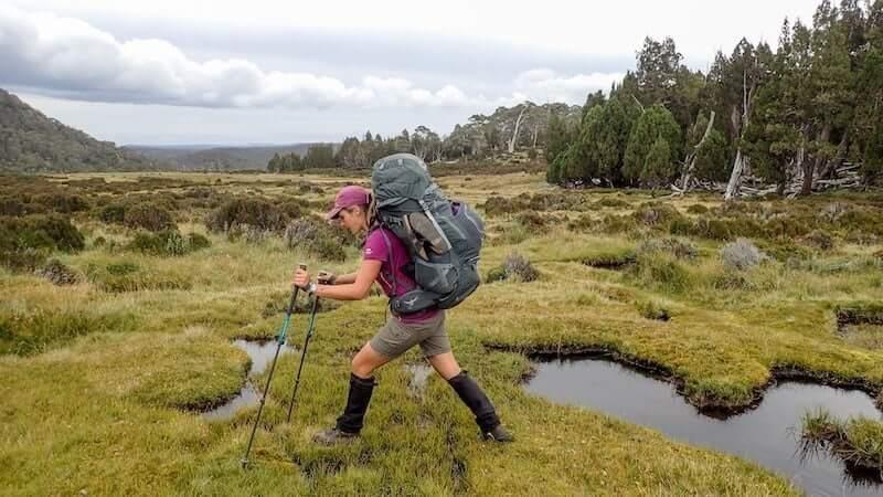 female hiker with poles steps through plain