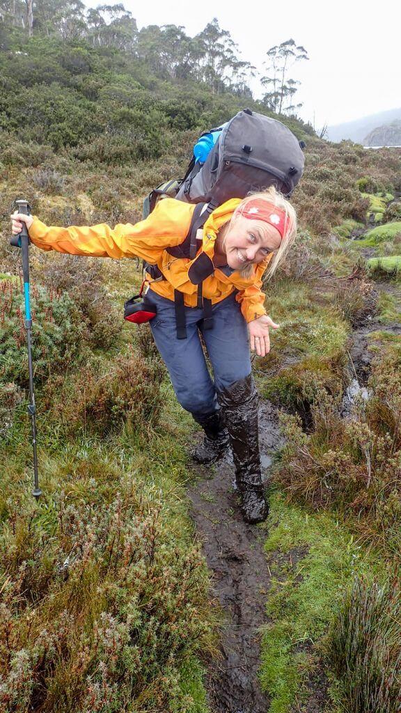 female hiker walks through mud